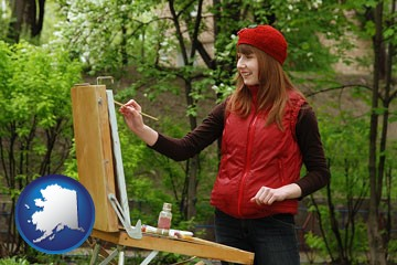 a female plein air artist painting with oils on a portable easel - with Alaska icon