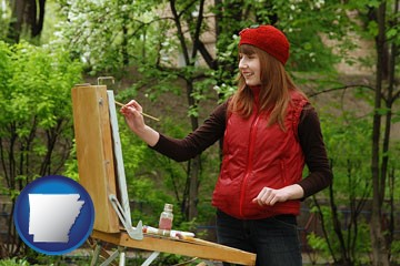 a female plein air artist painting with oils on a portable easel - with Arkansas icon