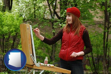 a female plein air artist painting with oils on a portable easel - with Arizona icon