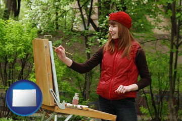 a female plein air artist painting with oils on a portable easel - with Colorado icon
