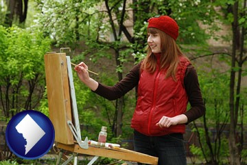 a female plein air artist painting with oils on a portable easel - with Washington, DC icon
