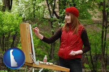 a female plein air artist painting with oils on a portable easel - with Delaware icon