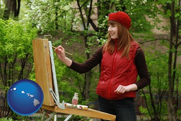 a female plein air artist painting with oils on a portable easel - with Hawaii icon