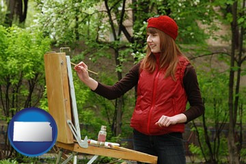 a female plein air artist painting with oils on a portable easel - with Kansas icon
