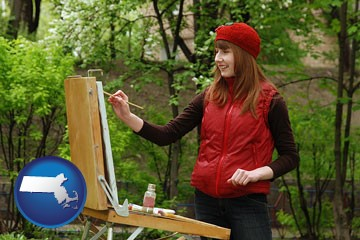 a female plein air artist painting with oils on a portable easel - with Massachusetts icon