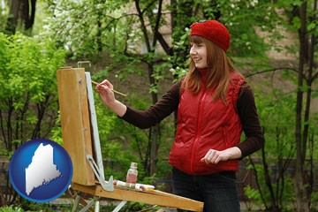 a female plein air artist painting with oils on a portable easel - with Maine icon