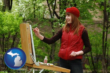 a female plein air artist painting with oils on a portable easel - with Michigan icon