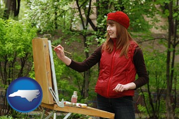 a female plein air artist painting with oils on a portable easel - with North Carolina icon