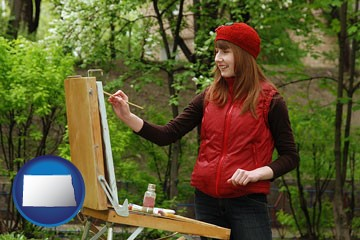 a female plein air artist painting with oils on a portable easel - with North Dakota icon
