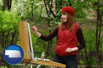 a female plein air artist painting with oils on a portable easel - with Nebraska icon