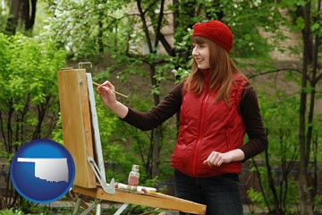 a female plein air artist painting with oils on a portable easel - with Oklahoma icon