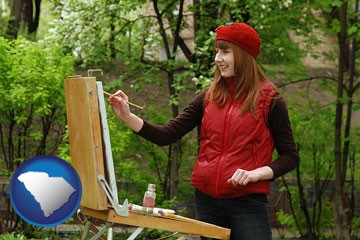 a female plein air artist painting with oils on a portable easel - with South Carolina icon
