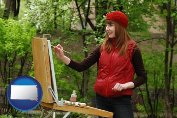 a female plein air artist painting with oils on a portable easel - with South Dakota icon