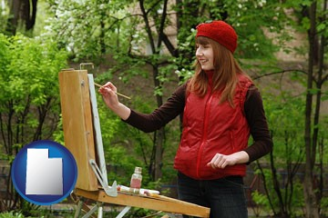 a female plein air artist painting with oils on a portable easel - with Utah icon