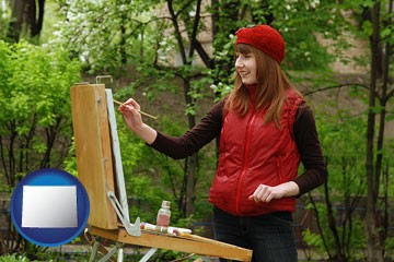 a female plein air artist painting with oils on a portable easel - with Wyoming icon