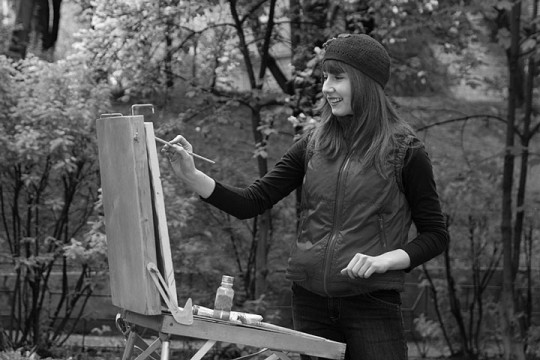 a female plein air artist painting with oils on a portable easel